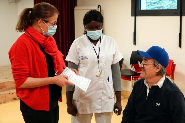 Murielle Henry, Directeur de la Résidence, remet son diplôme de vaccination à un résident.