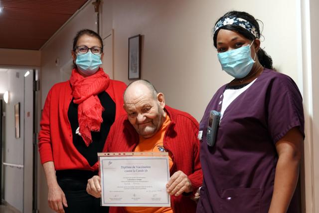 Un résident expose son diplôme de vaccination